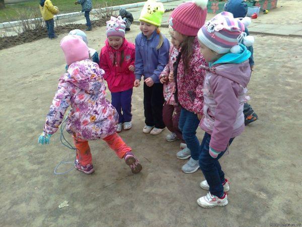 Девочки играют на улице со скакалкой