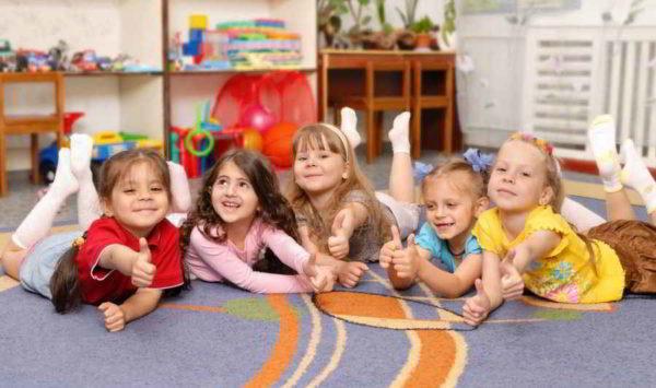 Девочки лежат на ковре и показывают большой палец