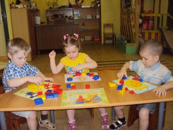 Два мальчика и девочка, сидя за столом, выполняют задания с блоками Дьенеша