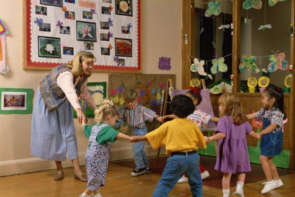 Дошкольники и педагог прыгают по кругу, держась за руки