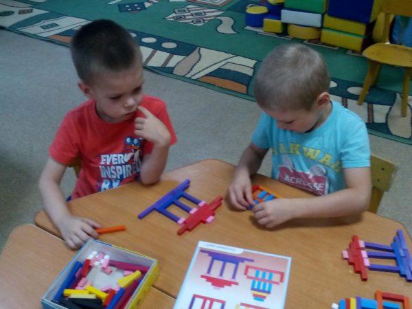 Два мальчика составляют изображения из палочек по схеме