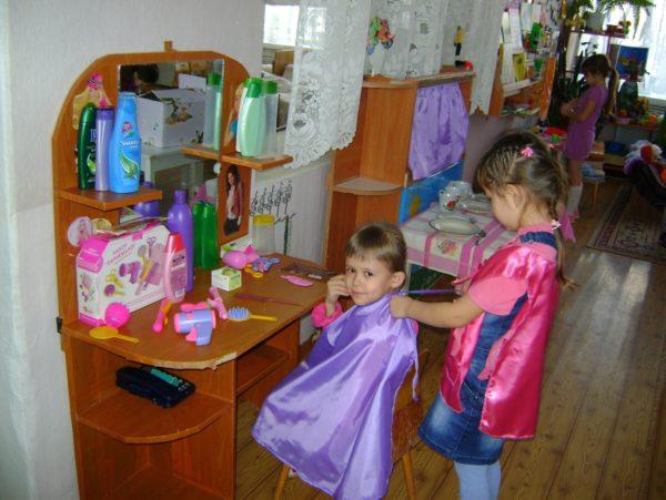 Две девочки играют в парикмахерскую в помещении группы