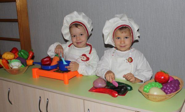 Две девочки в костюмах поваров играют в кухню
