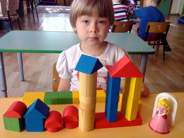 Девочка построила небольшой город из строительного материала для куклы