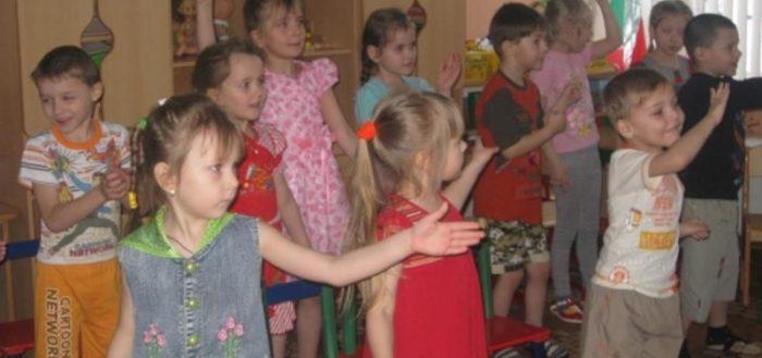 Группа детей выполняет двигательное упражнение