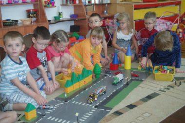 Группа дошкольников играет с машинками