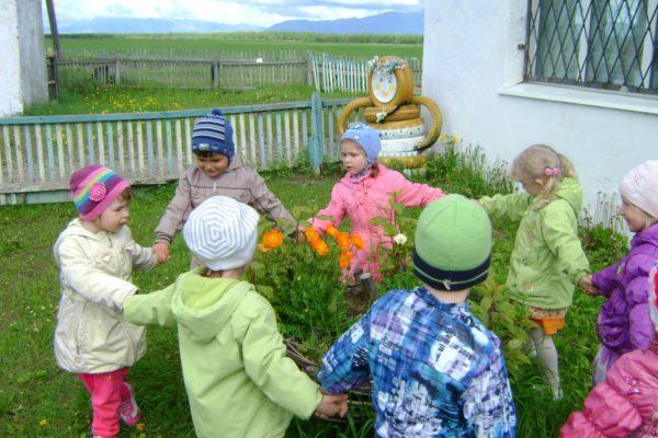 Дети водят хоровод вокруг клумбы с цветами
