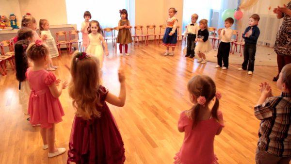 Дети стоят по кругу и хлопают в ладоши, одна девочка находится в центре