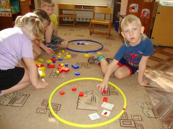 Дети играют на полу с блоками Дьенеша и обручами