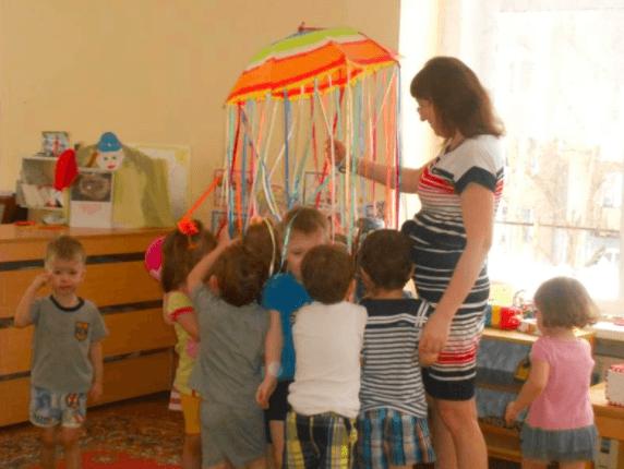 Дети и педагог держатся за разноцветные ленты, прикреплённые к куполу зонтика