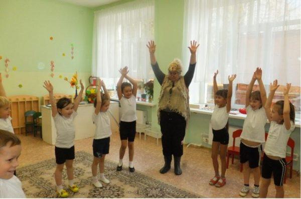 Дети в спортивной форме и педагог стоят, вытянув руки вверх