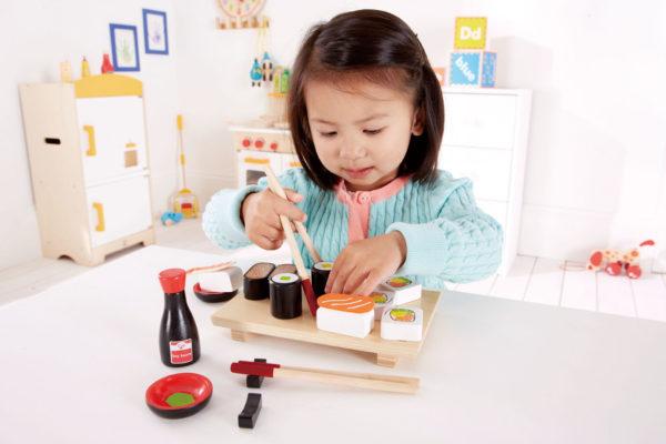 Девочка играет с пластмассовыми роллами