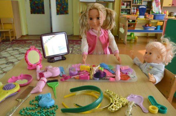 На столе разложены предметы для игры в парикмахерскую, рядом сидят две куклы