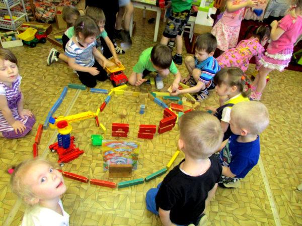 Дети сооружают постройку из деревянных кирпичиков на полу