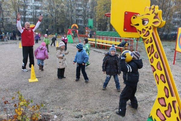 Инструктор по физкультуре и дети на спортивной площадке играют с мячом