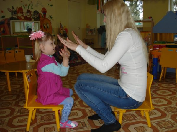 Девочка и педагог играют в «Ладушки»