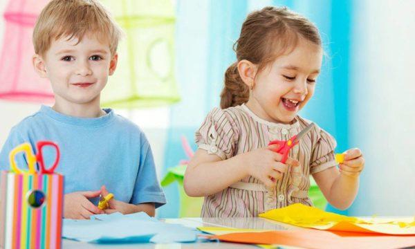 Мальчик и девочка вырезают из цветной бумаги