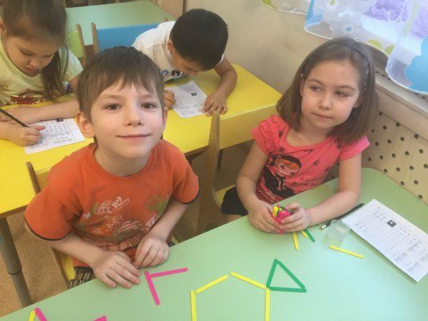 Мальчик и девочка играют со счётными палочками, сзади дети выполняют задания на листочках