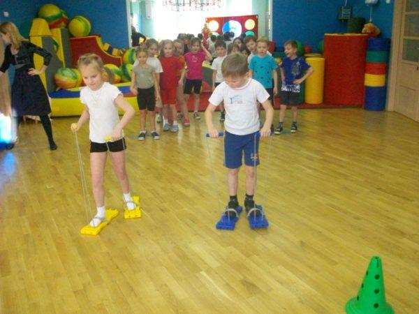 Мальчик и девочка передвигаются по залу с помощью специальных лыж, остальные дети наблюдают