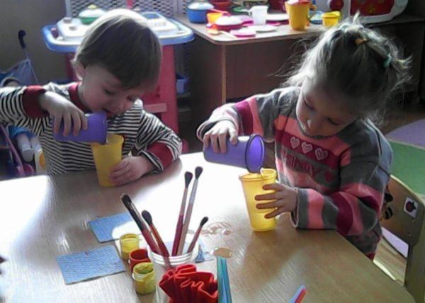 Мальчик и девочка переливают воду из стаканчиков