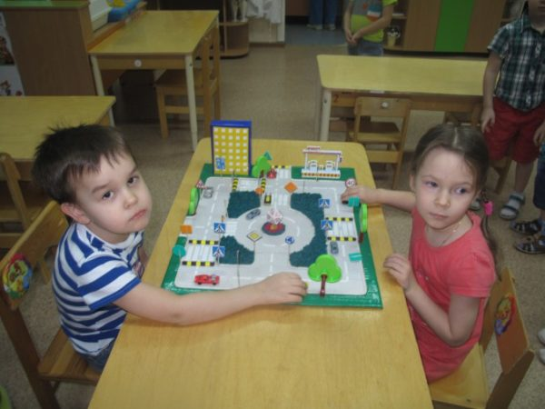 Мальчик и девочка играют в настольную игру по ПДД