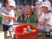 Мальчик ловит палкой шарики в тазу