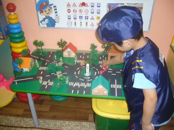 Мальчик передвигает машинки на макете проезжей части