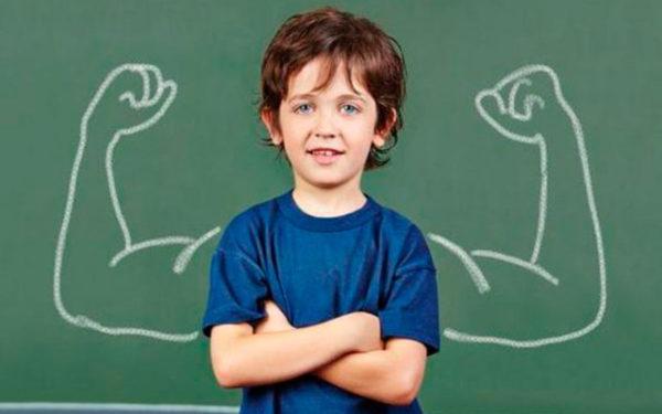 Мальчик стоит у доски, на которой изображены мускулистые руки