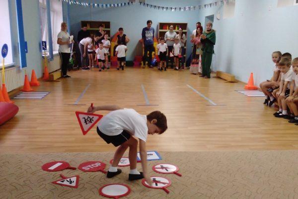 Мальчик разбирает дорожные знаки на полу в зале