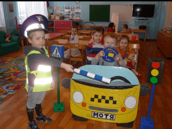 Мальчик-регулировщик останавливает макет такси с пассажирами