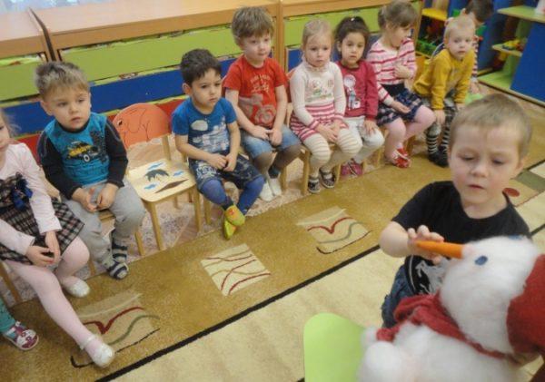 Мальчик трогает нос игрушки-снеговика, остальные дети сидят на стульчиках