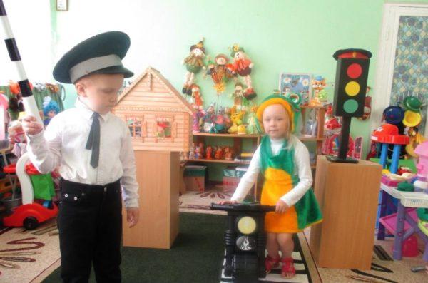 Мальчик в форме инспектора ДПС и девочка разыгрывают ситуацию на дороге