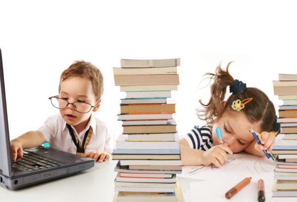 Мальчик в очках, девочка, ноутбук и две стопки книг
