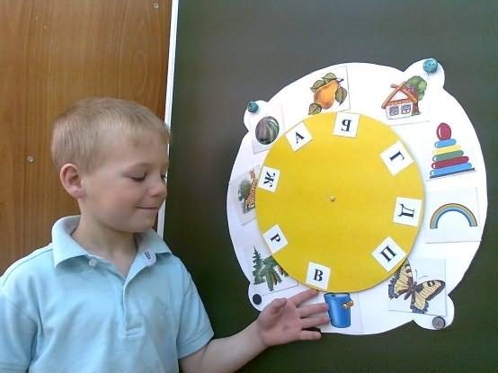 Мальчик на специальном макете соединяет изображения предметов с соответствующими буквами