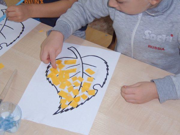 Мальчик выкладывает шаблон листика обрывками бумаги жёлтого цвета