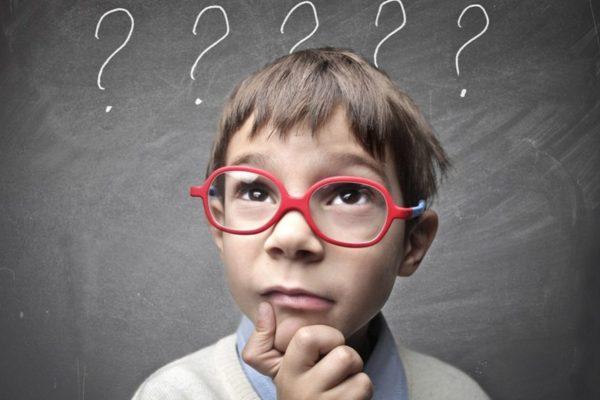 Мальчик в очках задумался на фоне доски с вопросами