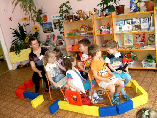 Дети и педагог сидят в импровизированной лодке, сделанной из строительных модулей
