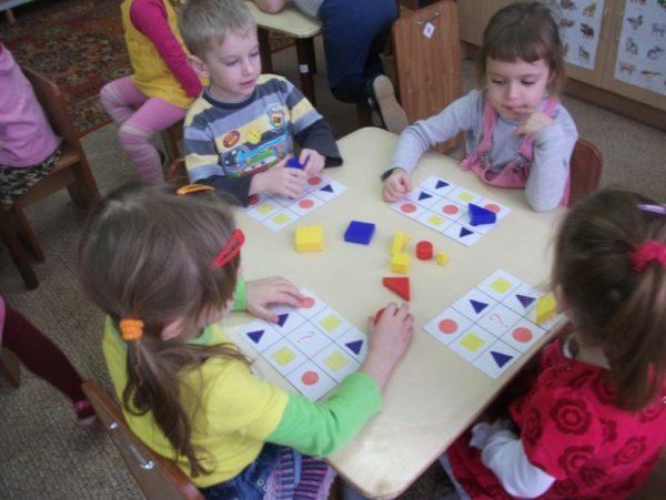 Дошкольники выполняют задание по карточкам с блоками Дьенеша
