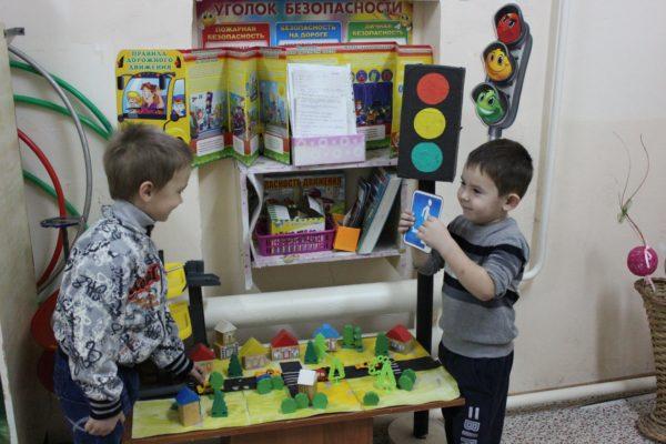 Один мальчик показывает другому картинку с изображением дорожного знака