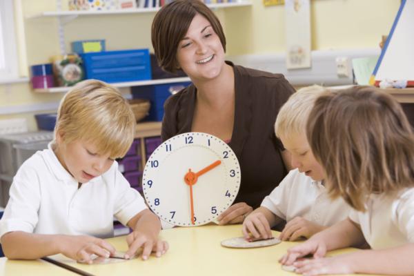 Педагог держит в руках настенные часы, дети выполняют задание