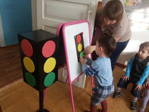 Педагог с мальчиком закрепляют зелёный кружок на макете светофора