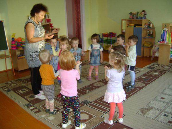Дети, стоя в кругу, повторяют движения руками вслед за педагогом