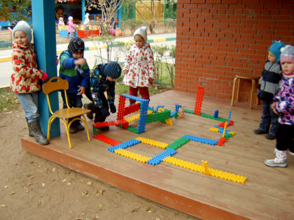 Дети стоят в беседке около постройки из крупного конструктора