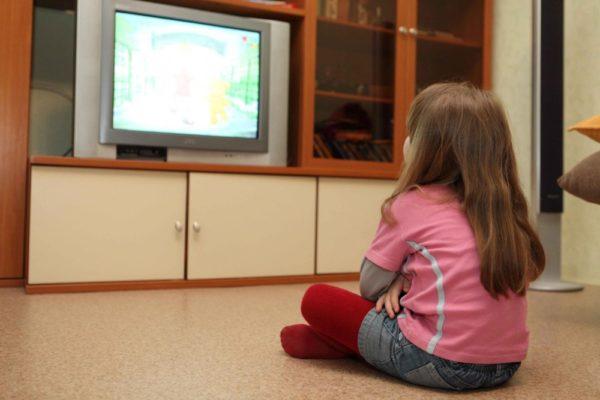 Девочка смотрит мультфильм по телевизору