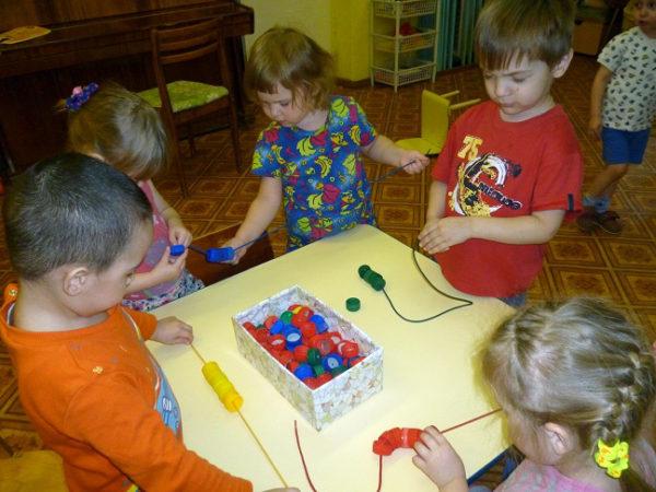Пятеро детей нанизывают цветные крышечки на шнурки