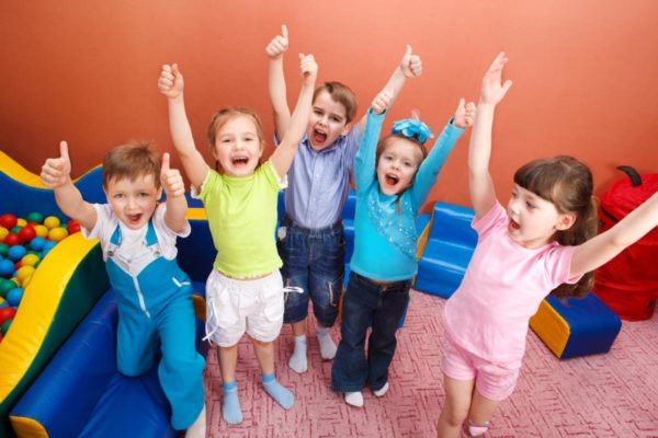 Пятеро улыбающихся детей стоят, подняв руки вверх