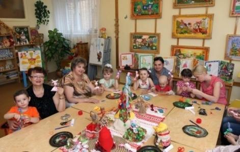 Родители и дети выполняют поделку куклу-мотанку