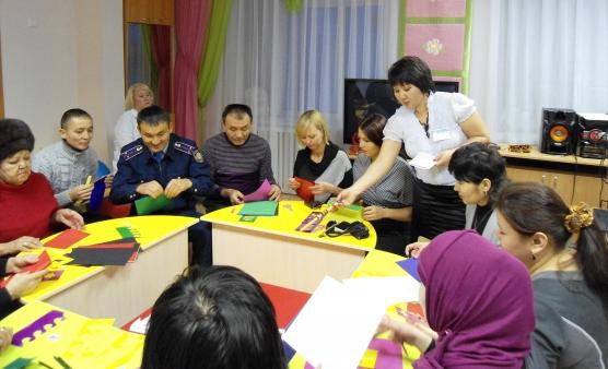 Родители за круглым столом вырезают из цветной бумаги