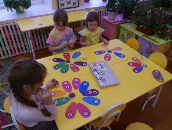 Три девочки выкладывают цифры на разноцветных бумажных лепестках