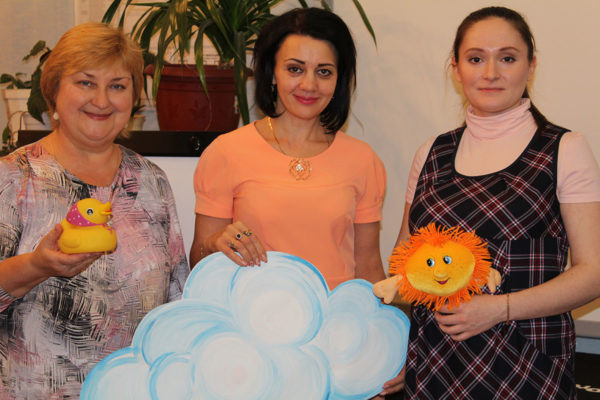 Три женщины держат в руках резиновую уточку, облако из бумаги и солнышко